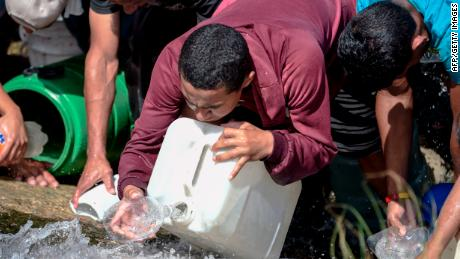 People collect water from a sewage canal at the river Guaire in Caracas on March 11, 2019, as a massive power outage continues affecting some areas of the country. - Venezuela's opposition leader Juan Guaido will ask lawmakers on Monday to declare a