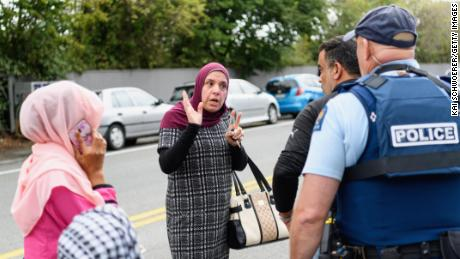 Members of the public react in front of the Masjid Al Noor Mosque.