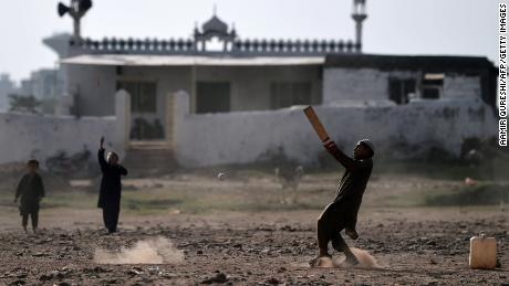 Afghan children play cricket at a refugee camp in Islamabad in October 2018.