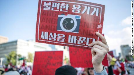 A woman holds up an anti-spy cam poster during a protest in Seoul in 2018.