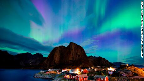 The northern lights dance across the night sky, high in the Arctic Circle.