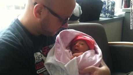 Eric Lohman is holding Rosie in the hospital in August 2012.