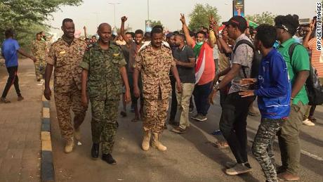 Sudanese protesters cheer Thursday for passing soldiers near military headquarters in Khartoum.