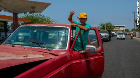Hinginio Acosta has been pushing his truck through a line of cars, waiting three hours to refill his tank at a gas station in Cabimas.