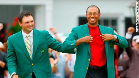 Tiger Woods receives the Green Jacket from previous champion Patrick Reed.