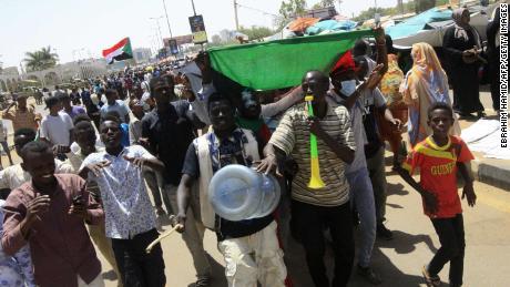 Sudanese protesters celebrate on April 13.