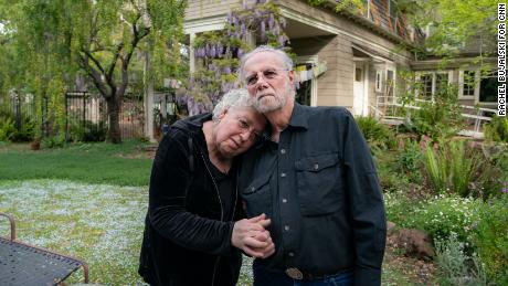"""Davis and Dafoe in front of their Palo Alto home. """"He's saving lives,"""" Dafoe says. """"Just by lying there."""""""