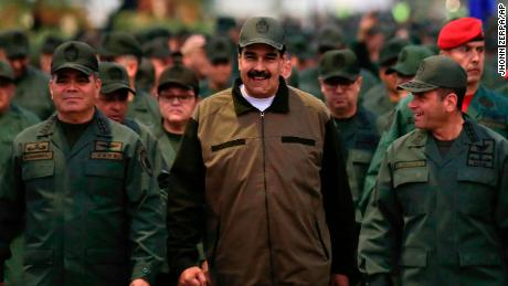 In this handout photo released by Miraflores Press Office, Venezuela's President Nicolas Maduro, center.