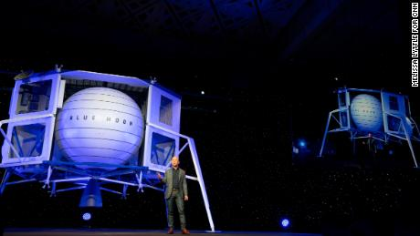 Jeff Bezos stands in front of a Blue Origin prototype of a lunar lander named Blue Moon.