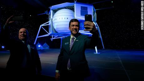 Attendees take selfies in front of the Blue Moon lunar lander after the presentation.