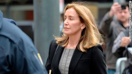 Actress Felicity Huffman is escorted into court Monday in Boston, where she is expected to plead guilty to one count of conspiracy to commit mail fraud and honest services mail fraud.