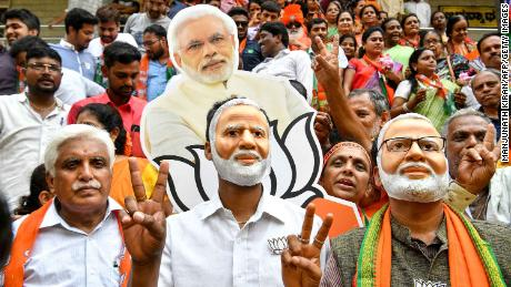 Supporters wear masks of Indian Prime Minister Narendra Modi and flash victory signs as they celebrate on the vote results day for India's general election on May 23, 2019.