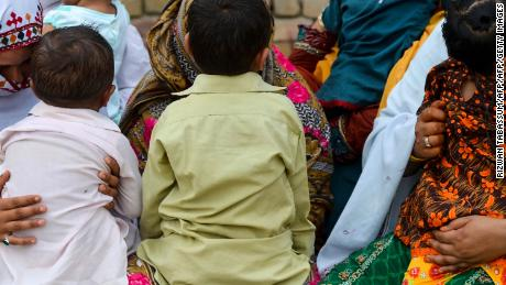Pakistani women hold their HIV infected children as they gather at a house at Wasayo village in Rato Dero in the district of Larkana of the southern Sindh province on May 8, 2019.