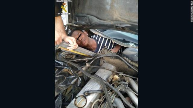 A man squeezed into a compartment built behind a car dashboard.
