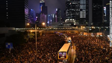 Buses drive through crowds of protesters outside the Legislative Council building as they demonstrate against the now-suspended extradition bill on June 16, 2019 in Hong Kong.