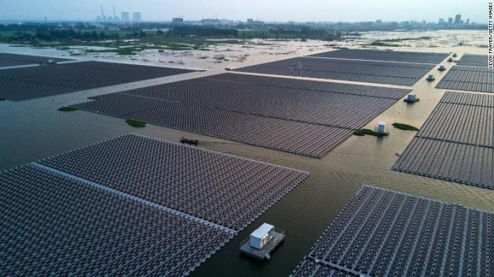 Chinese workers ride in a boat through a large floating solar farm project under construction by the Sungrow Power Supply Company in Huainan, Anhui province, China.