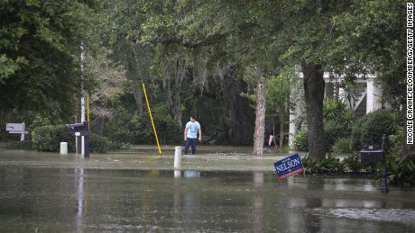 A resident stands in flood water outside a home near Lake Pontchartrain.