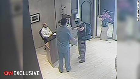 An Ecuadorian security guard, who abandoned his post, receives a package outside the embassy from a man in disguise on July 18, 2016. The man covered his face with a mask and sunglasses and was wearing a backpack.