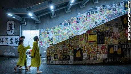 """People walk in front of a so-called """"Lennon Wall"""" where messages of support have been left for anti-extradition bill protesters on July 1, 2019 in Hong Kong."""
