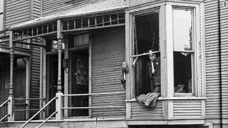 In this 1919 photo provided by the Chicago History Museum, police look through a broken window of a house during the race riots in Chicago. Broken furniture is strewn about the front yard.