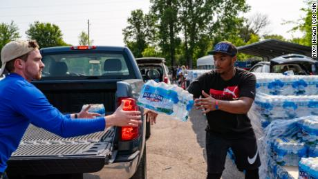 Daevion Marshall, 19, works at Greater Holy Temple Church and delivers cases of water into the cars of residents every week. He throws a case of water to Chris Blanco, a 24-year-old med student volunteer from Indiana University.