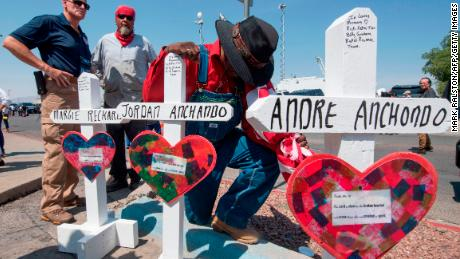 A man prays beside crosses bearing the names of Jordan and Andre Anchondo and the other victims of the El Paso massacre.