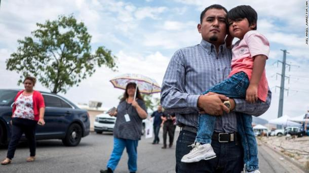 Ivan Flores, 27, poses with his son Derek, 4, near the site of the Walmart shooting in El Paso, Texas.