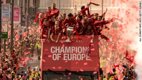 Liverpool coach Jurgen Klopp (C) holds the Champions League trophy as he stands with his players during an open-top bus parade around the city.
