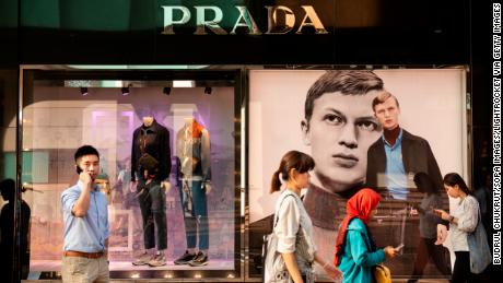 People walk past a Prada store in Hong Kong. The Italian fashion house says sales have been hurt by the protests.