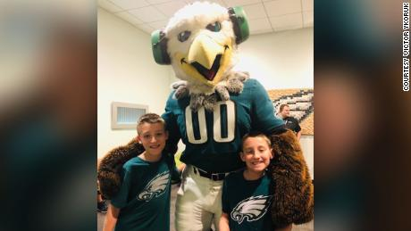 Twins Jack and Ryan Ykoruk, who have autism, play with Swoop, the Philadelphia Eagles mascot.