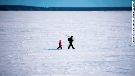 A man and his son go ice-fishing in Vaasa area, on the frozen Bothnia sea (Baltic Sea), on March 20, 2018, in Vaasa.