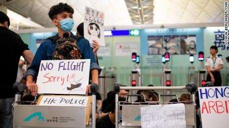 Protesters at Hong Kong International Airport block the entrance to the security checkpoint on Tuesday, August 13.