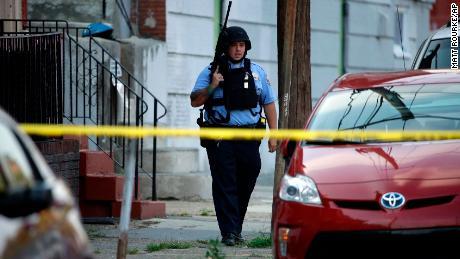 A police officer patrols the block near the shooting scene in Philadelphia.