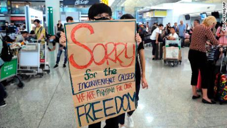 A protester shows a placard to stranded travelers during a demonstration at the Airport in Hong Kong, Tuesday, Aug. 13, 2019.