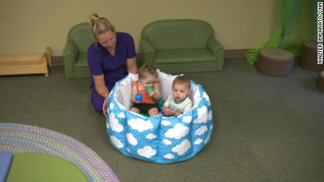 A day care teacher gives attention to a few months of age.