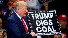Republican presidential candidate Donald Trump holds a cartel in support of coal during a 2016 rally. As president, the Trump administration has eased many regulations aimed at stopping climate change.