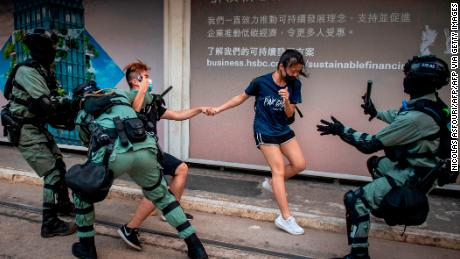 Police chase down a couple wearing facemasks in the central district in Hong Kong on October 5, 2019.