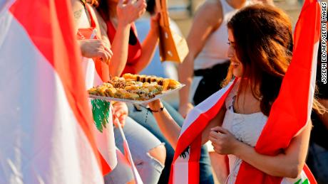 A Lebanese protester offers sweets to people during demonstrations Monday, north of Beirut.