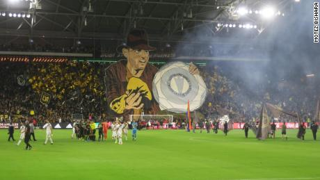 The North Stand at LAFC displays a banner depicting star forward Carlos Vela as Indiana Jones lifting the recently won MLS Supporter's Sheild.