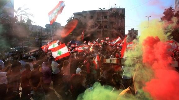 Demonstrators wave flags as they gather in the southern city of Sidon on October 19.