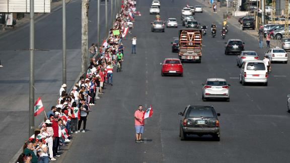 Protesters hold hands to form a human chain along a coastal highway near Beirut on Sunday, October 27.