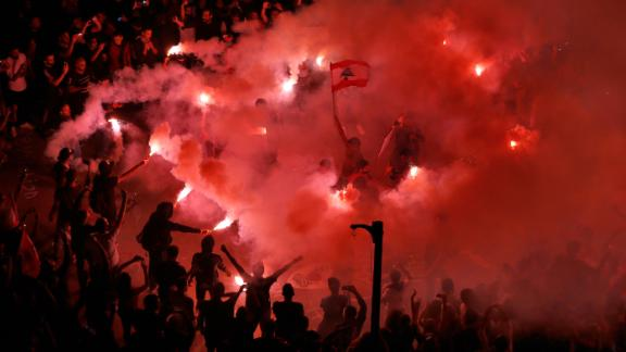 Protesters light flares and chant slogans against the Lebanese government on Sunday, November 3.