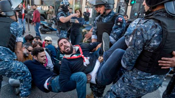 Riot police remove anti-government protesters who were occupying an intersection in Beirut, Lebanon, on Monday, November 4.