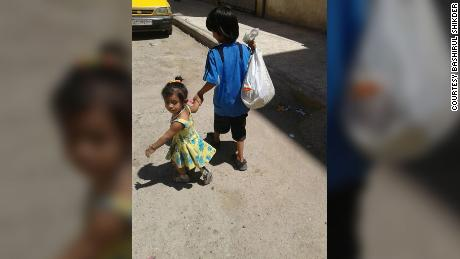 Yusuf holds the hand of his toddler sister Zahra as they walk down a street in Raqqa.