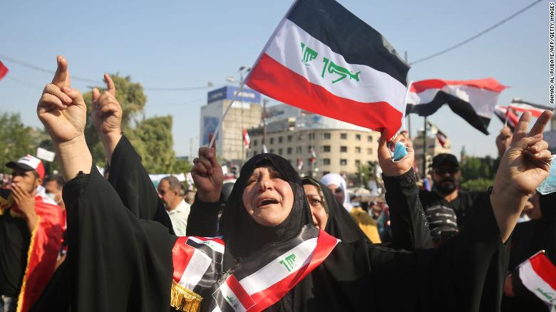 Iraqi women chant slogans and wave national flags as they take part in a protest in the capital Baghdad's Tahrir Square during anti-government protests on November 4, 2019.