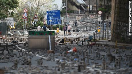 People walk on Saturday, November 16, among bricks laid on a road by protesters near a university in Hong Kong.