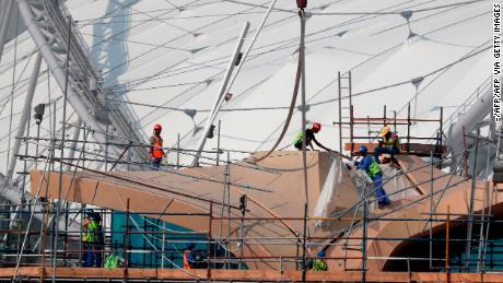 I lavoratori sono raffigurati sui ponteggi al Khalifa International Stadium di Doha.