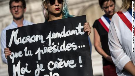 "An activist holds a placard reading ""Macron while you preside I'm dying"" during a demonstration dedicated to the memory of the women killed by their spouse or ex-spouse since the beginning of the year and against the violence against women, in front of the Paris city hall, on August 28."