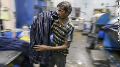 A worker unloads jeans from a fabric dyeing machine at a factory in India. (Dhiraj Singh/Bloomberg/Getty Images)