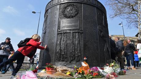 Persone toccare il Hillsborough Monumento ai caduti, dove i nomi delle vittime sono stati scritti in perpetuo.